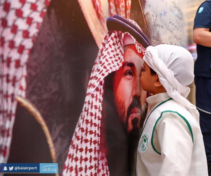 طفل يقبّل صورة ولي العهد في مطار الملك عبدالعزيز بجدة